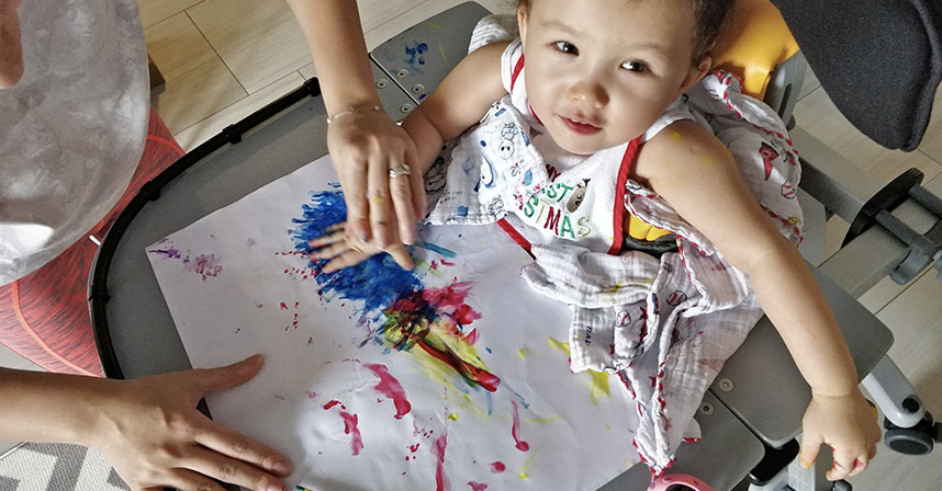 standing with AADC   AADC News   Rylae-Ann has physical therapy while in her stander, by painting with her hands on a colorful sheet of paper, with the assistance of one of her parents
